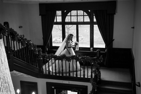 Bride walking down the manor staircase