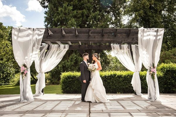 Bride and groom under the pergola at Swynford Manor