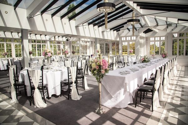 Decorative dining tables inside with roses and candles Cambridgeshire weddings