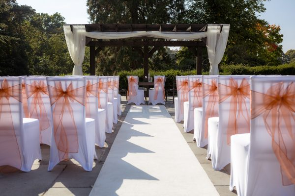 Decorated outdoor wedding aisle with bow backed chairs Cambridgeshire weddings
