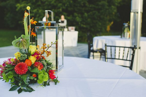 Colourful flower bouquet and lantern on table at outside Cambridgeshire wedding