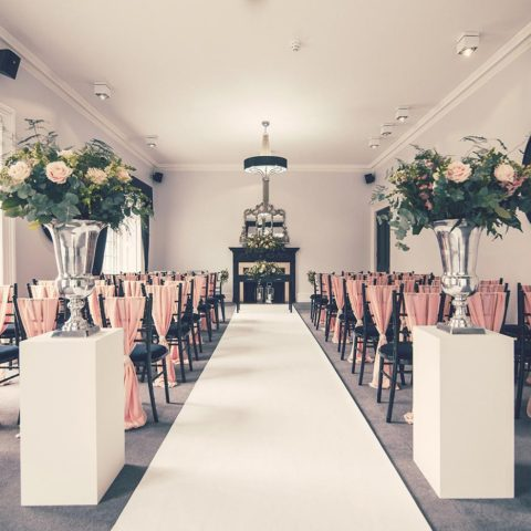 Stylish silver and pink wedding ceremony decorations at Swynford Manor