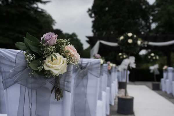 Bow backed chairs decorated with rose bouquets at Cambridgeshire wedding