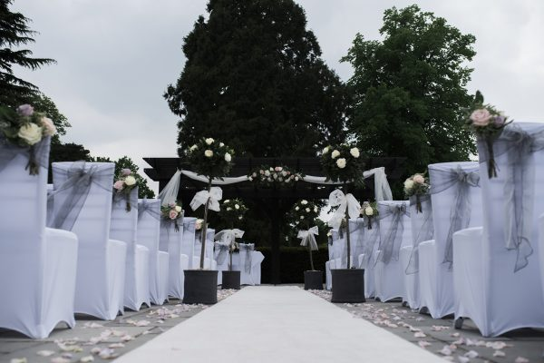 Aisle decorated with ribbon, bows and rose bouquets at Cambridgeshire wedding outside