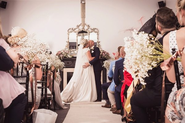 Bride and grooms first kiss in a contemporary wedding venue