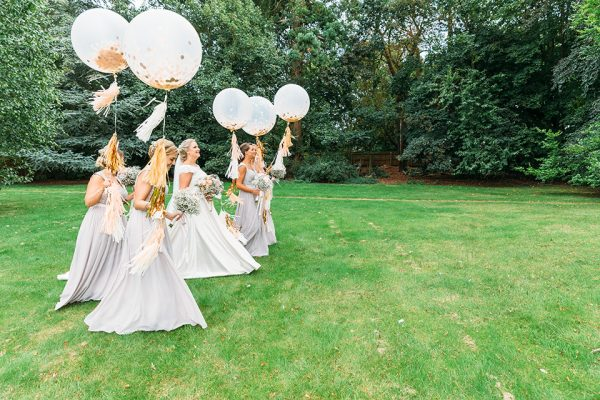 Bridesmaids at Swynford Manor wearing stunning silver bridesmaids dresses - confetti balloons