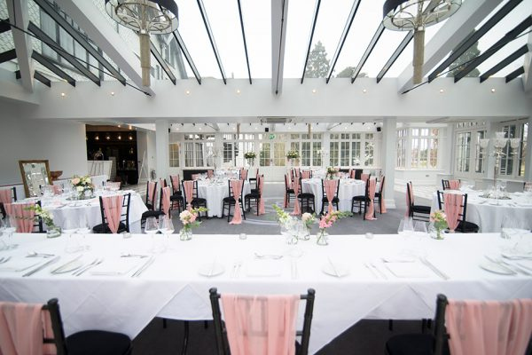 Pink flowers in glass jars in The Garden Room are perfect spring wedding colours
