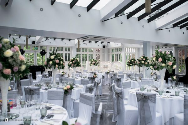 The Garden Room decorated with a gorgeous silver wedding theme and floral centerpieces - white roses