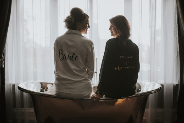 A bride and bridesmaid sit in one of Swynford Manor's infamous copper baths for a fun wedding photo