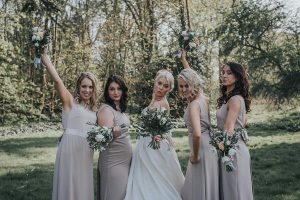 The bride and her bridesmaids strike a fun pose for an outdoor wedding photo at Swynford Manor