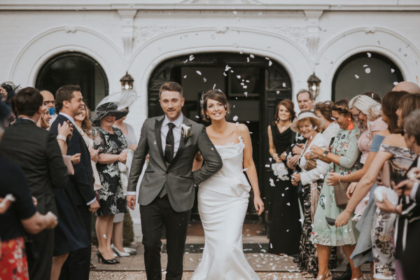 A bride and groom enjoy a confetti moment after their wedding ceremony at Swynford Manor