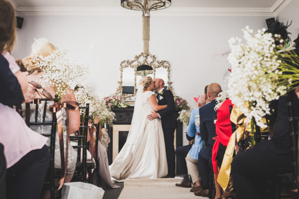 The bride and groom share their first kiss during their wedding ceremony at Swynford Manor wedding venue