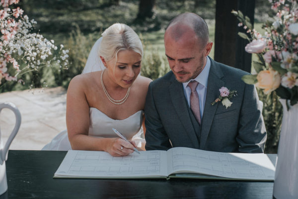 The bride and groom sign the wedding register after their outdoor wedding ceremony at Swynford Manor