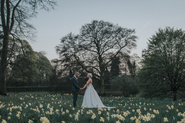 A bride and groom stand among daffodils on their spring wedding day at Swynford Manor wedding venue in Cambridgeshire