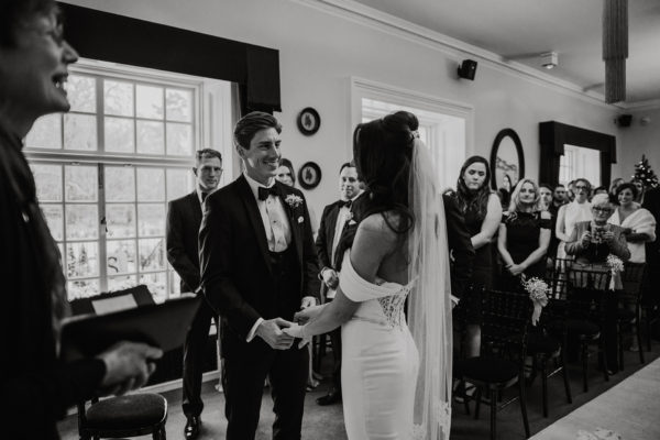 the bride and groom say their wedding vows in front of guests during their wedding ceremony at Swynford Manor