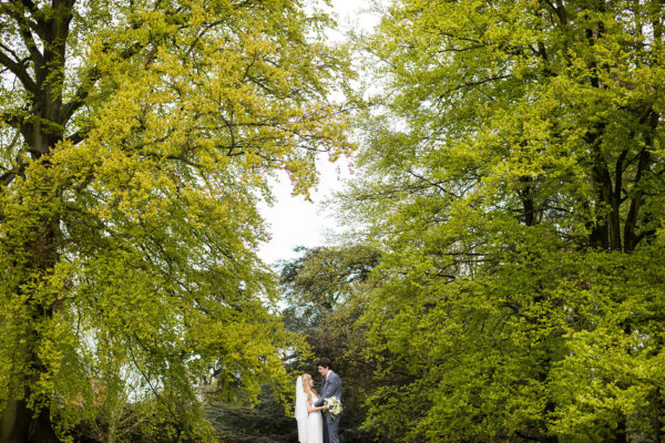 The bride and groom make use of the woodland surrounding Swnyford Manor for their wedding photos