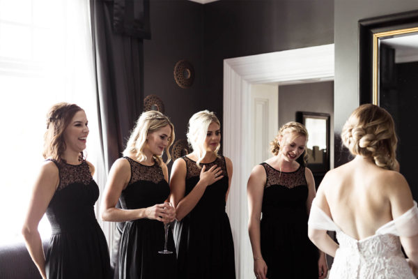 A bride and her bridesmaids who wear black dresses get ready in the bridal preparation suite at Swynford Manor
