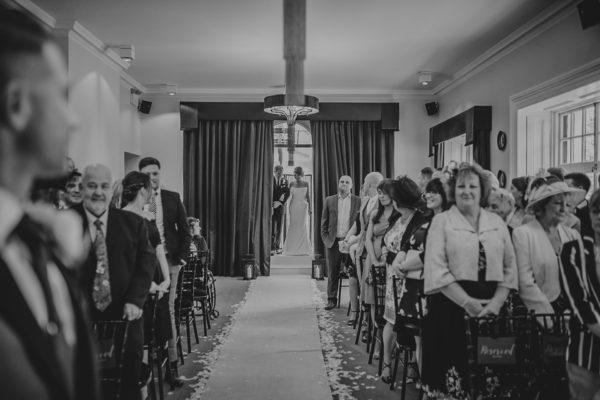 The bride makes her entrance into the wedding ceremony at Swynford Manor as her groom looks on