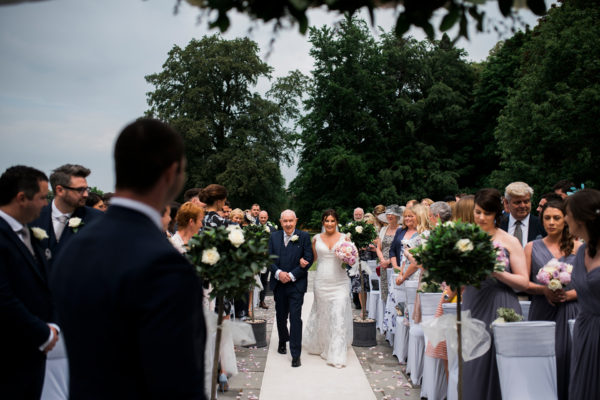 The bride and her father walk down the aisle at an outdoor wedding ceremony at Swynford Manor