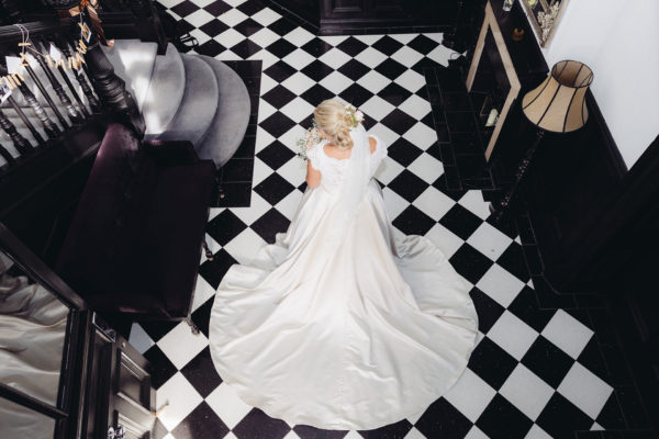 A bride shows off her wedding dress against Swynford Manor's black and white checked flooring