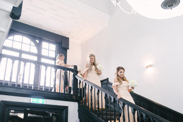 A bridesmaid helps the bride down the grand staircase at Swynford Manor towards the wedding ceremony