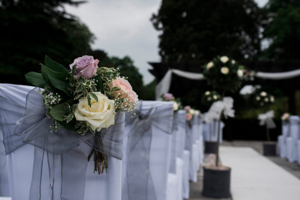 Floral posies adorn the chairs for an outdoor wedding ceremony at Swynford Manor wedding venue in Cambridgeshire