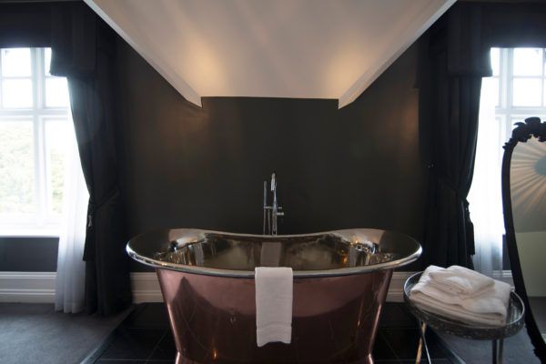 A copper bath sits within a bedroom for a boutique hotel feel at Swynford Manor