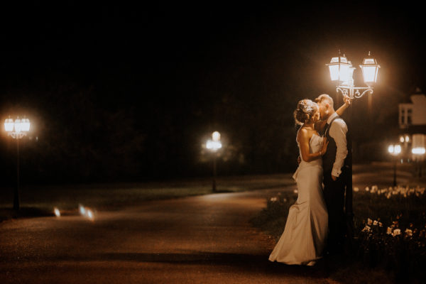 The new husband and wife share a kiss under dramatic lighting for a stunning evening wedding photo