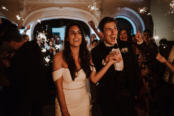 The new husband and wife walk through a sparkler exit at the end of their wedding day at Swynford Manor