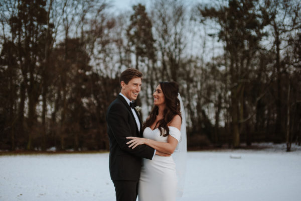 The newlyweds head outside in to the snow during their winter wedding at Swynford Manor