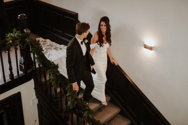 The newlyweds walk down the grand staircase on their wedding day at Swynford Manor