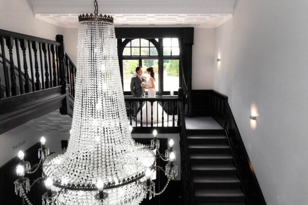 Newlyweds stand at the top of the staircase at Swynford Manor for a stunning wedding photo