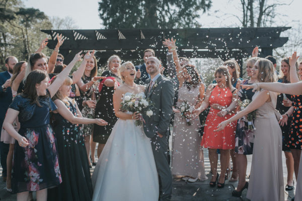 Newlyweds enjoy a confetti moment after their outdoor wedding ceremony ay Swynford Manor