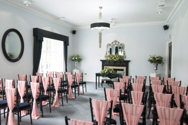 Pink sashes adorn the chairs for a wedding ceremony at Swynford Manor wedding venue