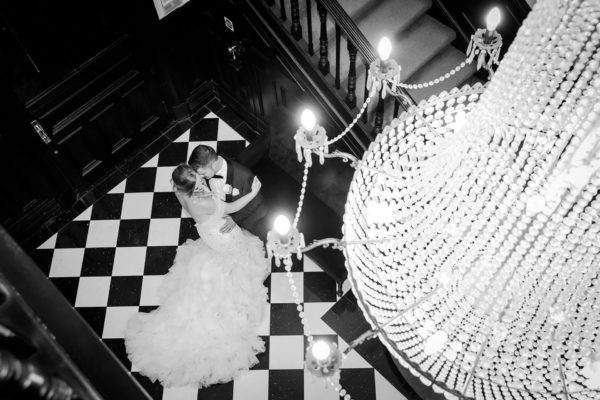 Newlyweds post for a romantic wedding photo under the chandelier at Swynford Manor