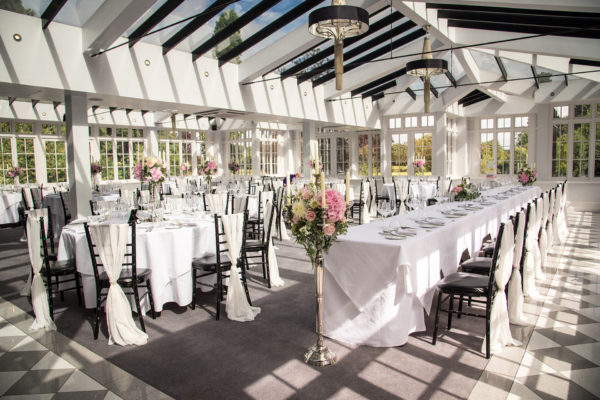 The Garden Room at Swynford Manor is set up for a wedding breakfast that includes a top table