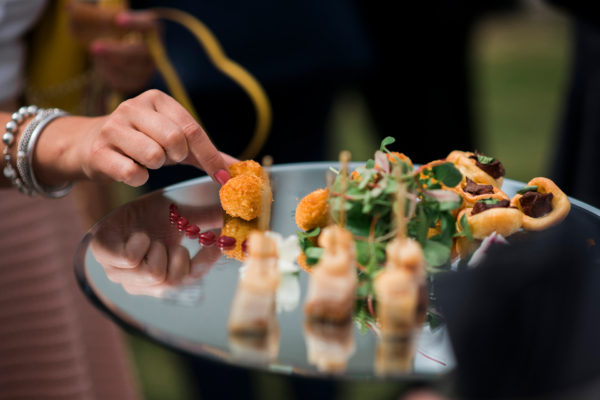 A guest helps themselves to a delicious wedding canape during a drinks reception at Swynford Manor wedding venue in Cambridgeshire