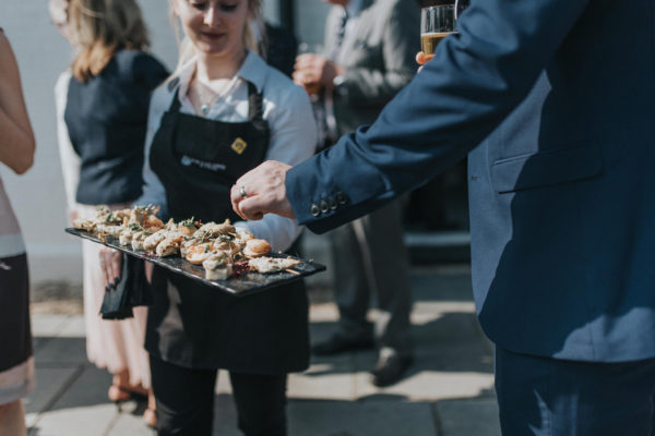 Wedding guests are given a delicious selection of wedding canapes during an outdoor drinks reception at Swynford Manor
