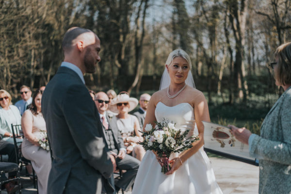 The happy couple say their wedding vows during an outdoor wedding ceremony at Swynford Manor wedding venue in Cambridgeshire