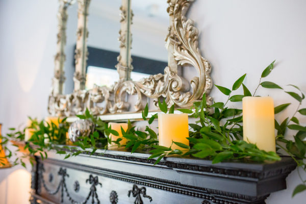 Candles and greenery adorn the fireplace in the Study at Swynford Manor wedding venue in Cambridgeshire