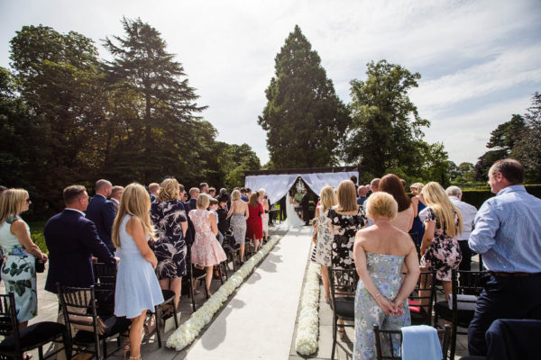Wedding guests watch an outdoor wedding ceremony at the Cambridgeshire country house wedding venue