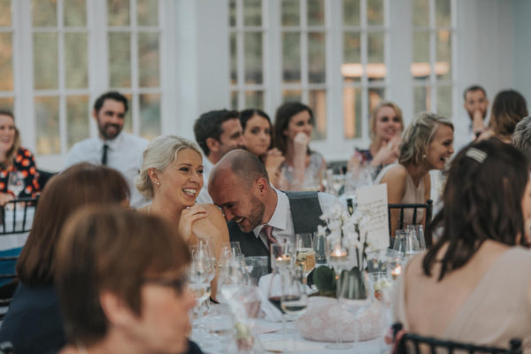 The bride and groom giggle during the wedding speeches in the Garden Room at Swynford Manor