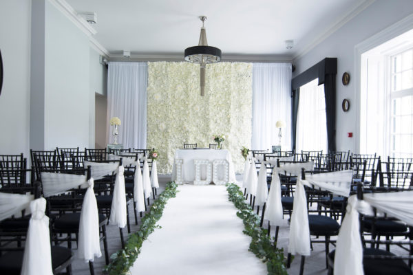 A white backdrop is used in The Study at Swynford Manor for a dramatic wedding ceremony set up