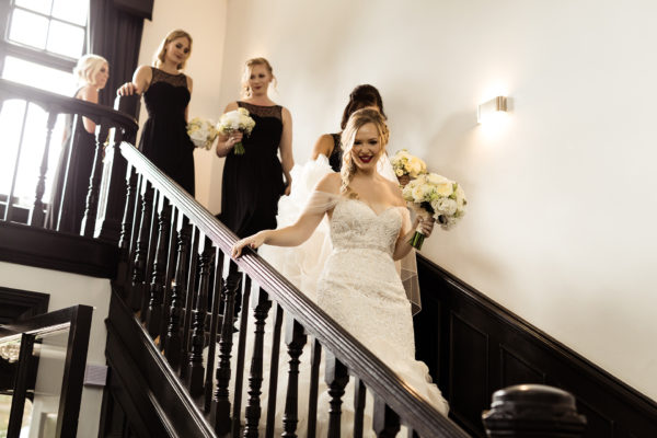 The bridal party make their way down the grand staircase at Swynford Manor