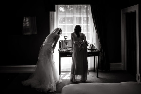 A bride and her bridesmaid watch guests arrive for a wedding at Swynford Manor boutique wedding venue in Cambridgeshire