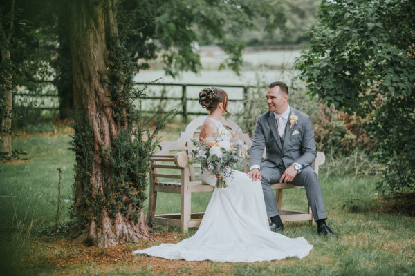 A bride and groom explore the country garden at Swynford Manor wedding venue in Cambridgeshire