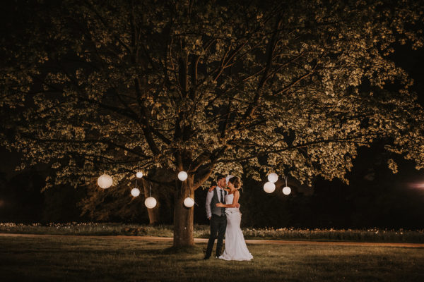 A bride and groom make the most of the gardens during their evening wedding reception at Swynford Manor