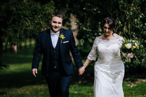 A bride and groom explore the gardens during their summer wedding at Swynford Manor