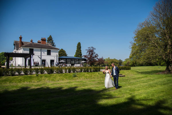 A bride and groom explore the grounds of Swynford Manor on their summer wedding day
