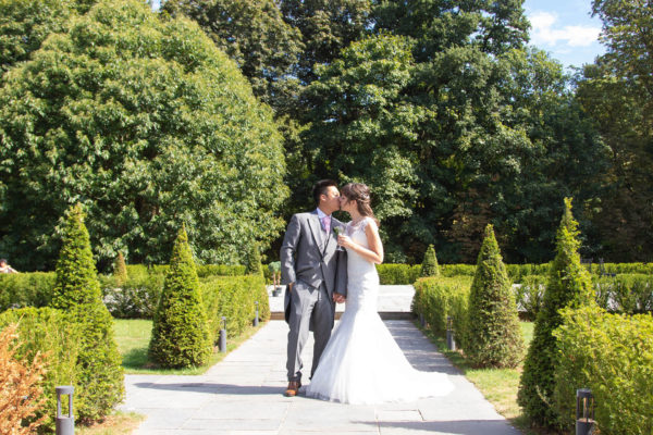 A bride and groom kiss as they enjoy an outdoor wedding reception at Swynford Manor
